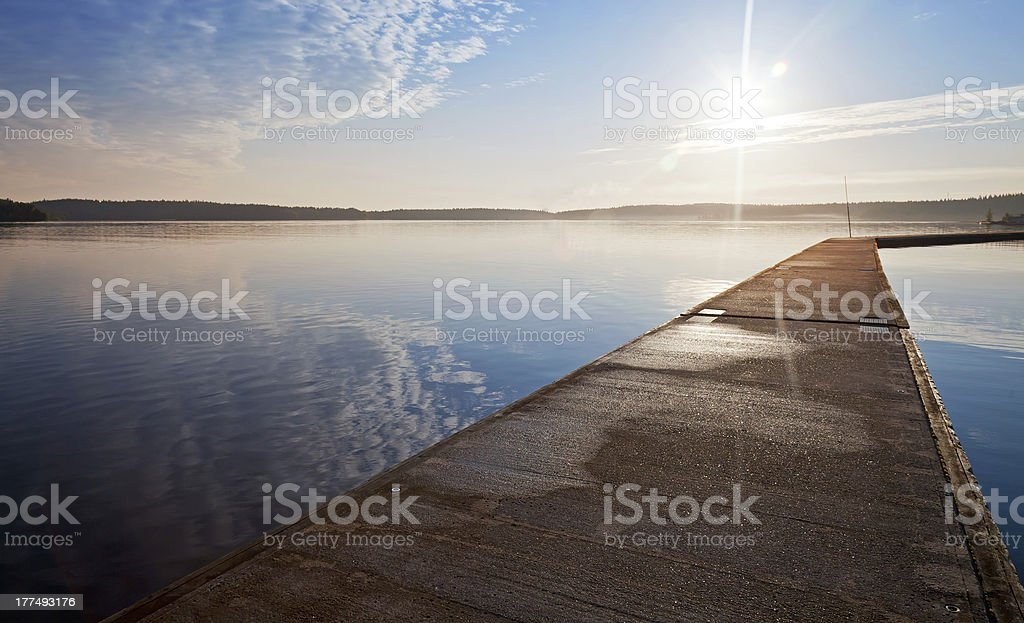 Empty concrete pier in the light of raising sun royalty-free stock photo