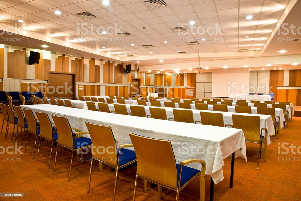 Empty conference room with rows of tables and chairs stock photo