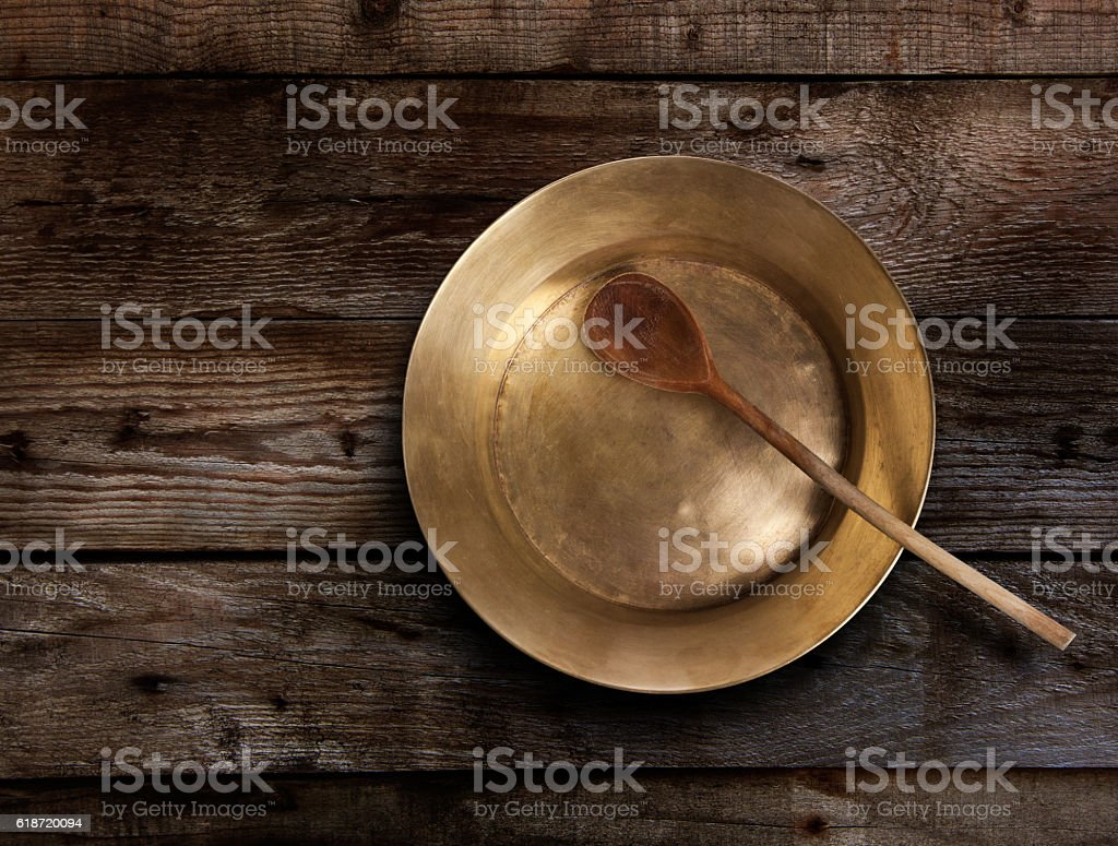 Empty copper tray, wooden spoon on a wooden table stock photo