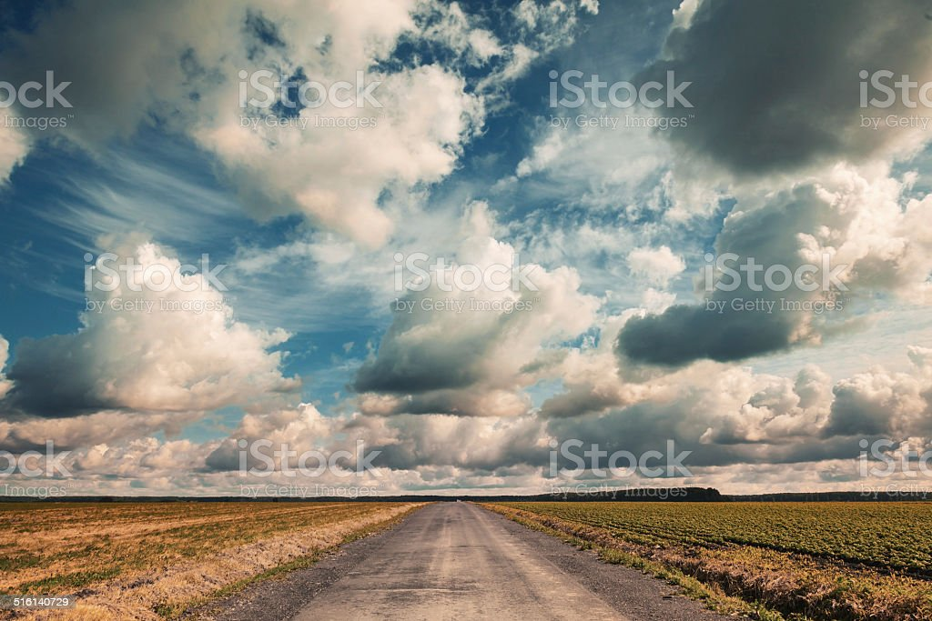 Empty country road with dramatic cloudy sky. Vintage toned effect stock photo
