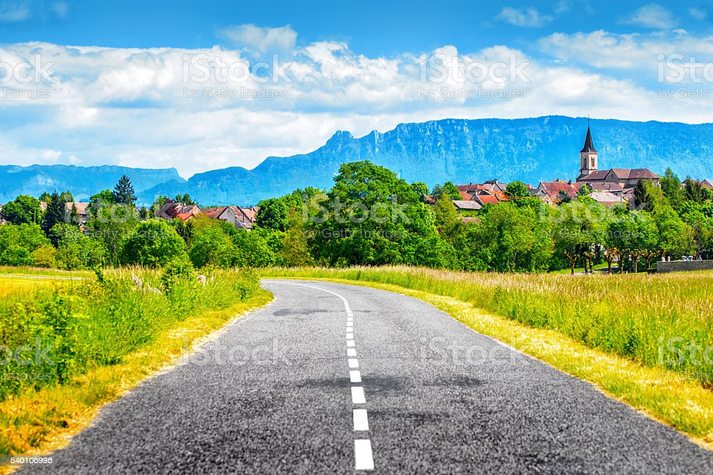Empty countryside road with old french village and Alps mountains stock photo