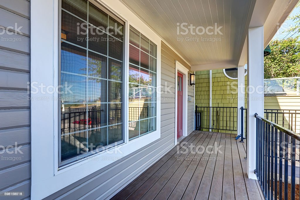 Empty covered porch with black metal railings and columns. stock photo