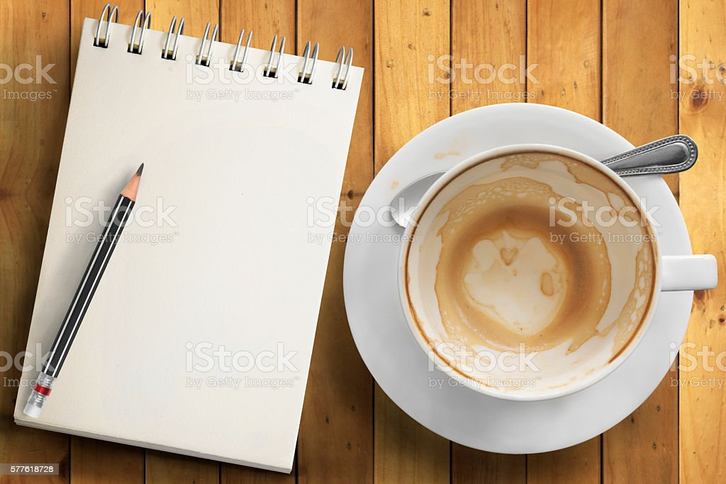 Empty cup of coffee and empty notepad stock photo