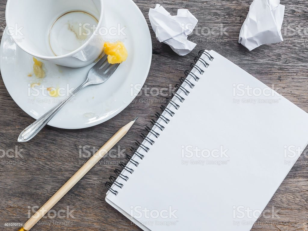 Empty cup of coffee and plate with notepad stock photo