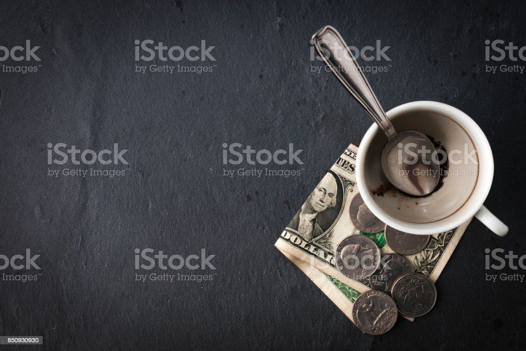 Empty cup with spoon and cash, top view stock photo