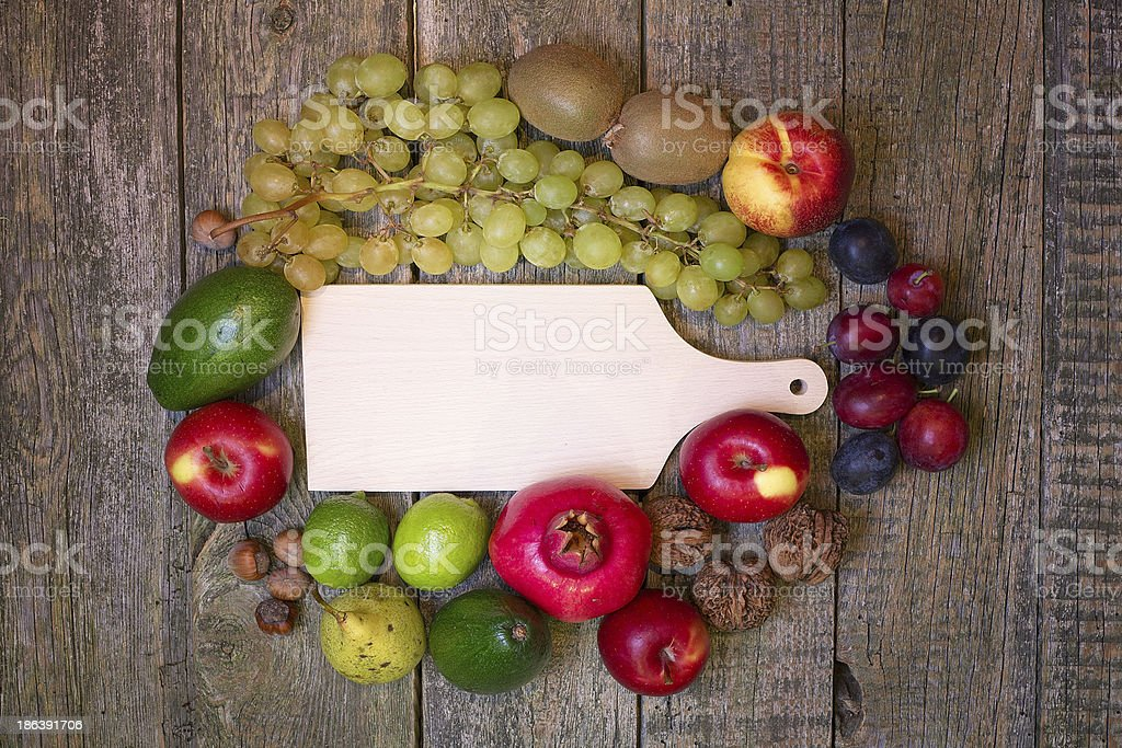 Empty cutting board on a wooden background with fruit. royalty-free stock photo