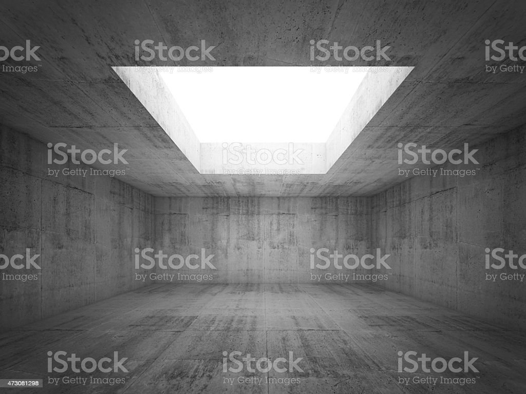 Empty dark concrete room interior with white opening in ceiling, stock photo