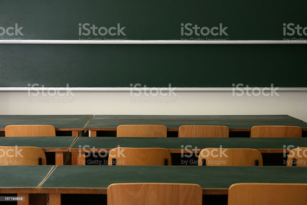 Empty desks and chairs in a college classroom royalty-free stock photo