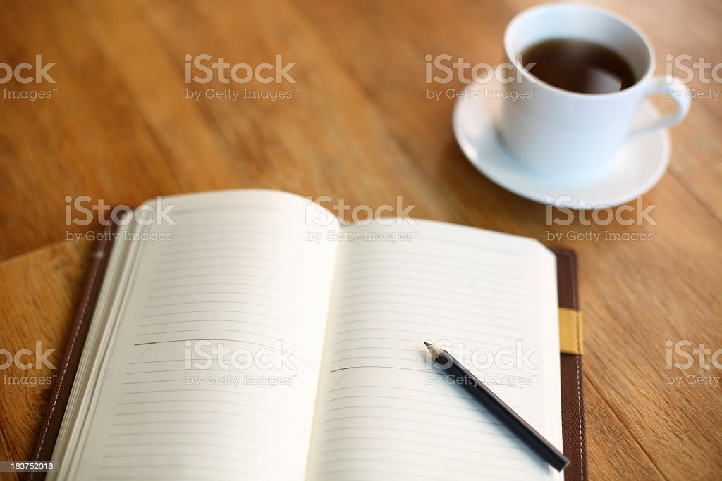 Empty diary with pencil and cup of coffee on wooden table royalty-free stock photo