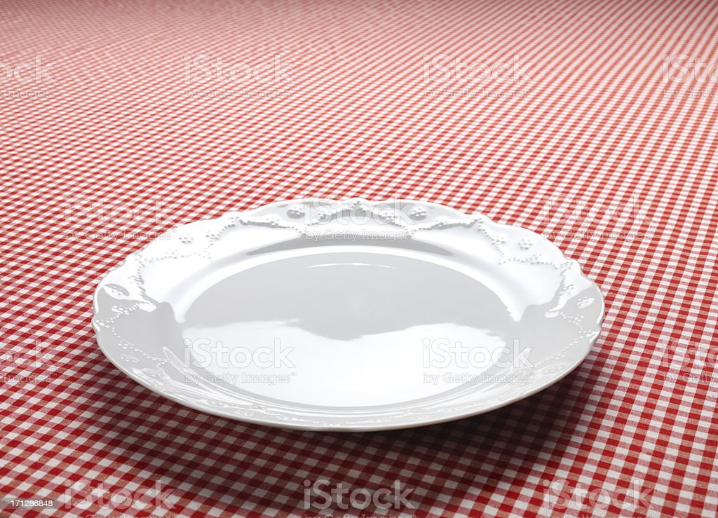 Empty Dish On The Checkered Tablecloth stock photo