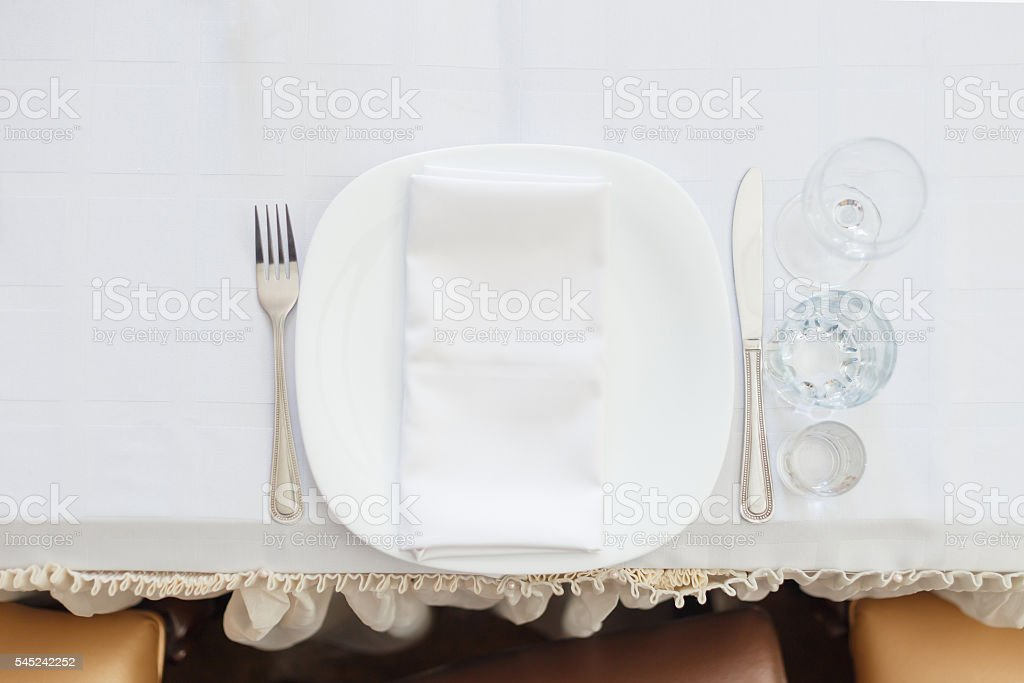 Empty dish with knife and fork on white table stock photo