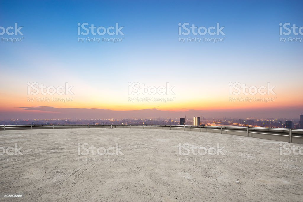 empty floor front of cityscape at sunrise stock photo
