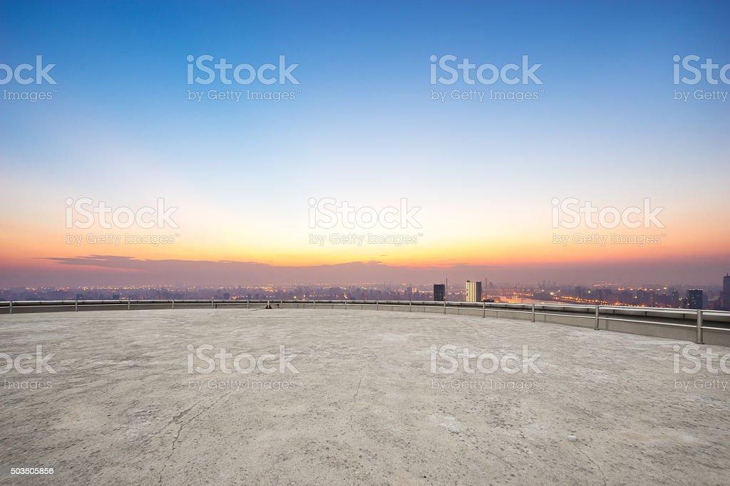 empty floor front of cityscape at sunrise stock photo