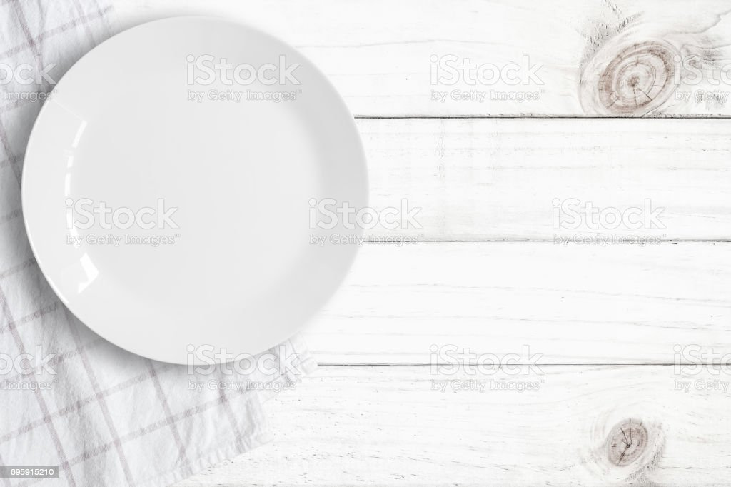 Top view of empty food plate put on tablecloth and wood table., All...