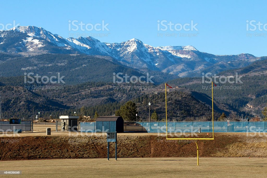 Empty football field and snowcapped mountains stock photo