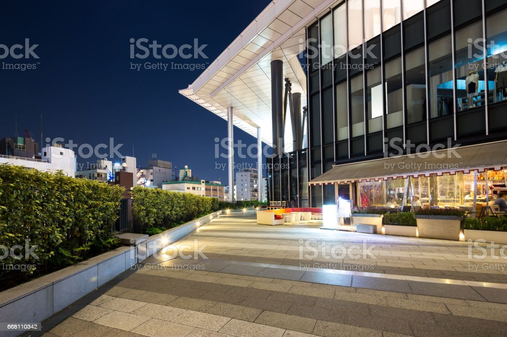 empty footpath outside of modern building at night stock photo