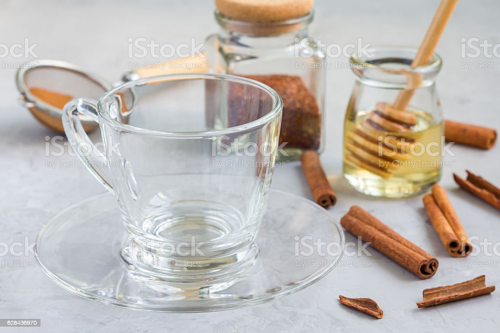 Empty glass cup and ingredients for healthy rooibos red tea stock photo