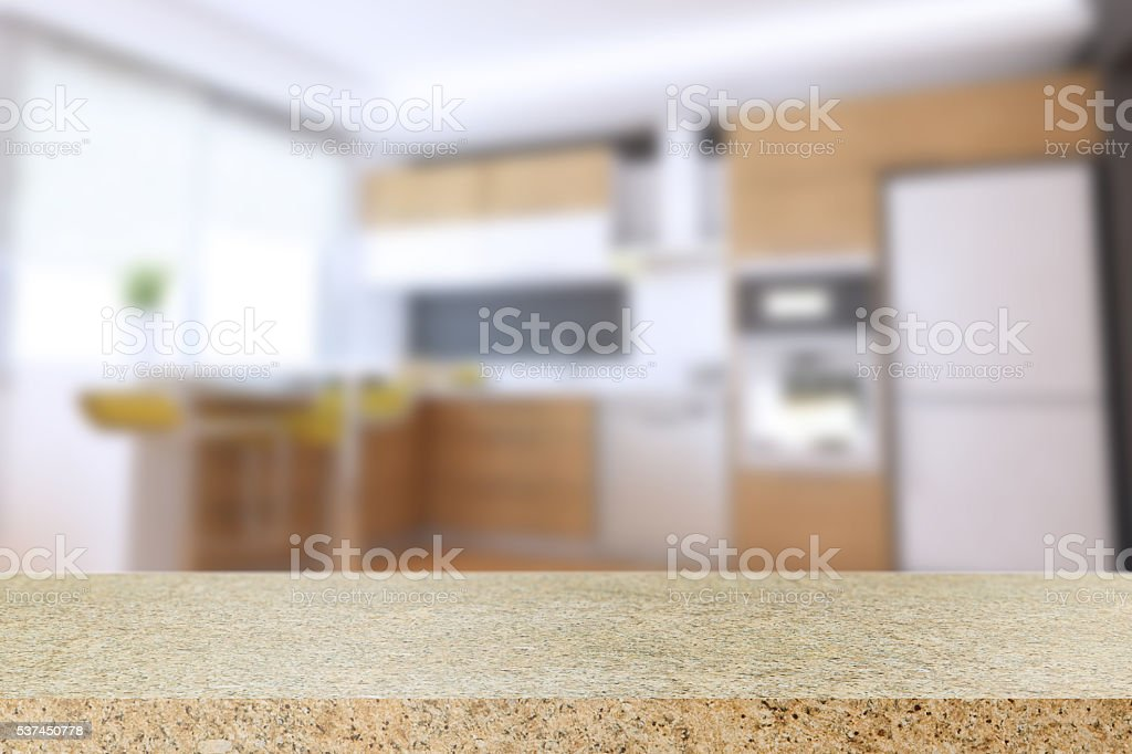 Empty venetian gold granite table and blurred kitchen background.