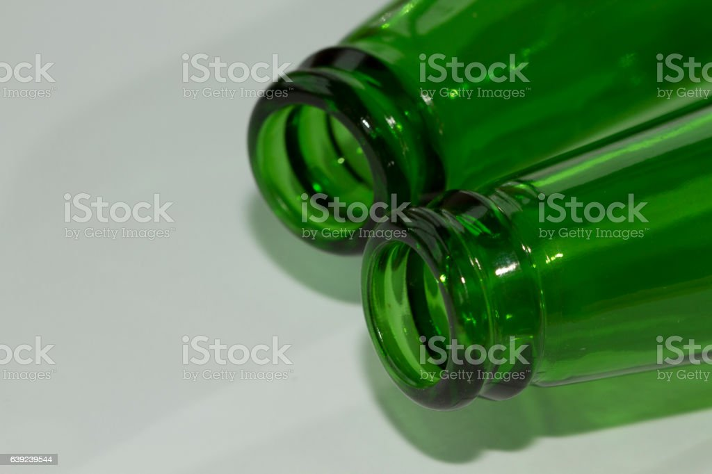 Empty green beer bottle necks on white background