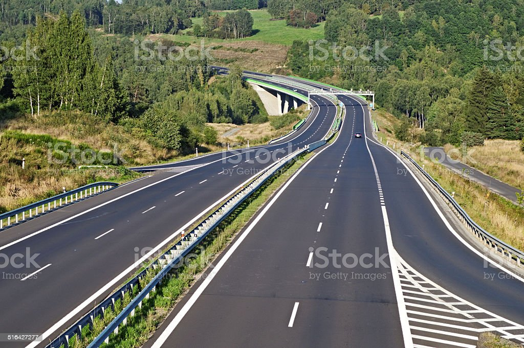 Empty highway between forests in the landscape stock photo