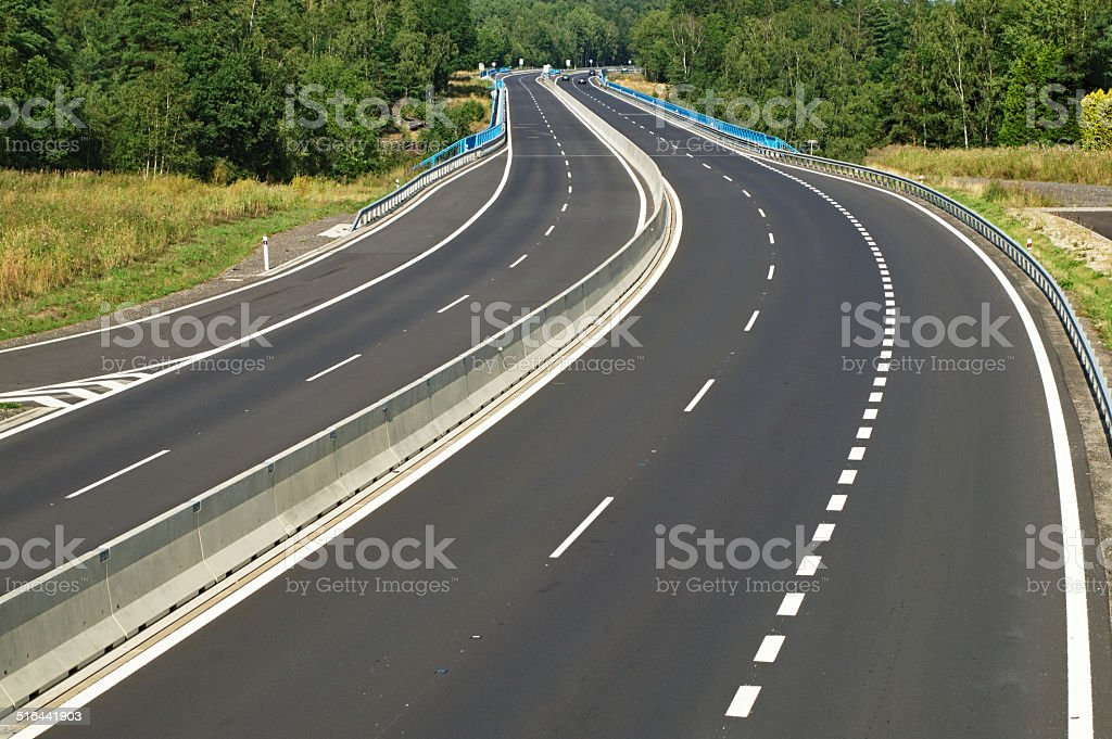 Empty highway disappearing into the trees in the forest stock photo
