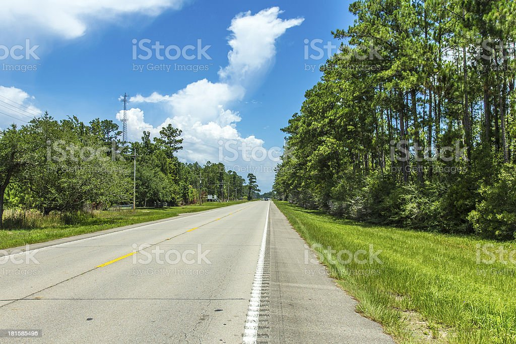 empty highway in america with trees and blue sky royalty-free stock photo
