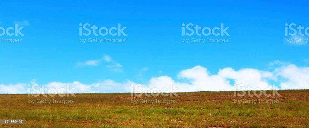 Empty hillside landscape with field and clouded sky stock photo