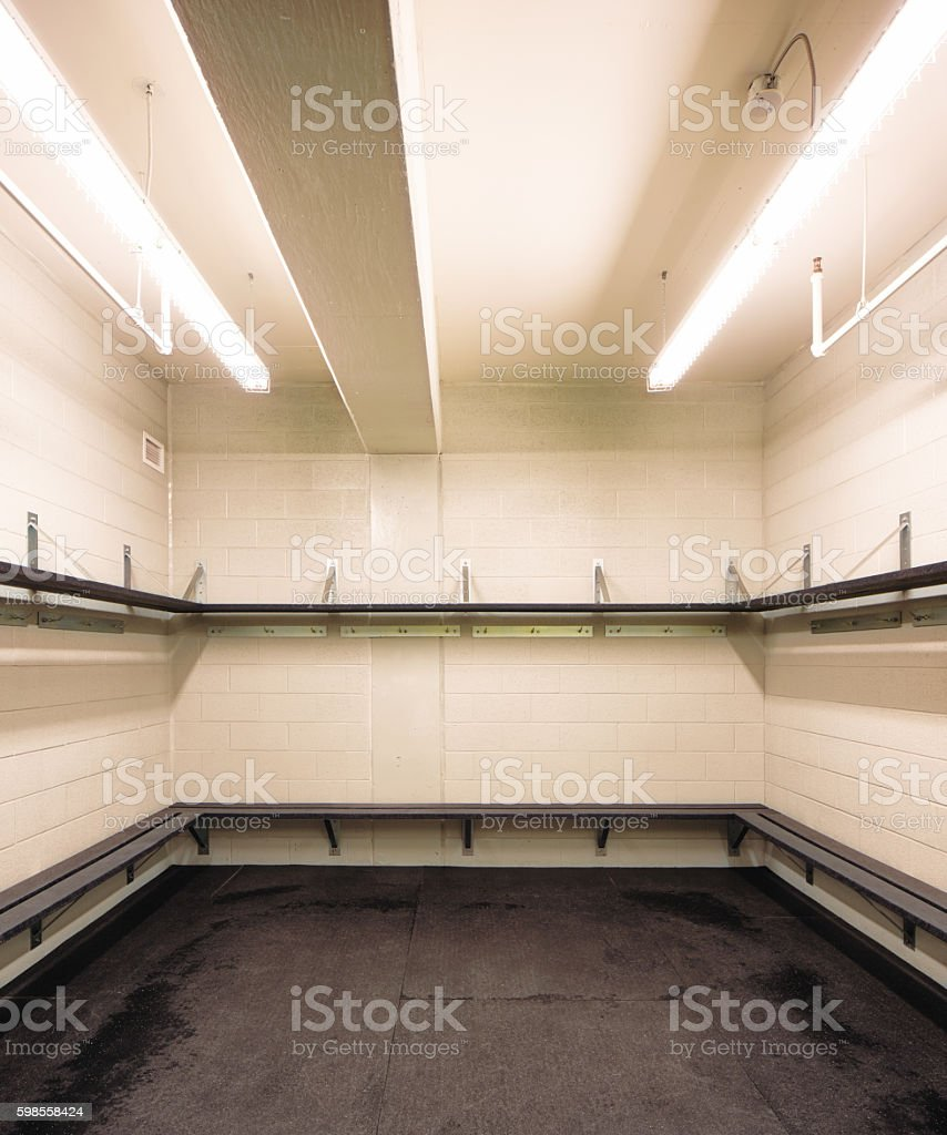Empty hockey rink sports changing room with benches and tablets, lit...