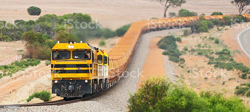 Empty iron ore train with orange wagons in hills stock photo
