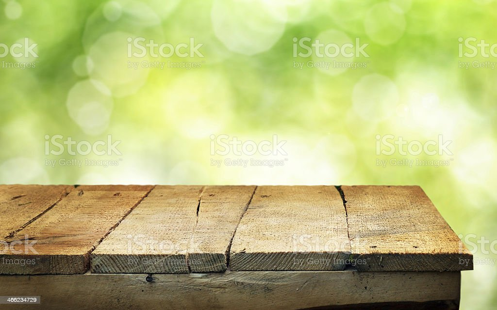 Empty light brown wooden table on green background stock photo