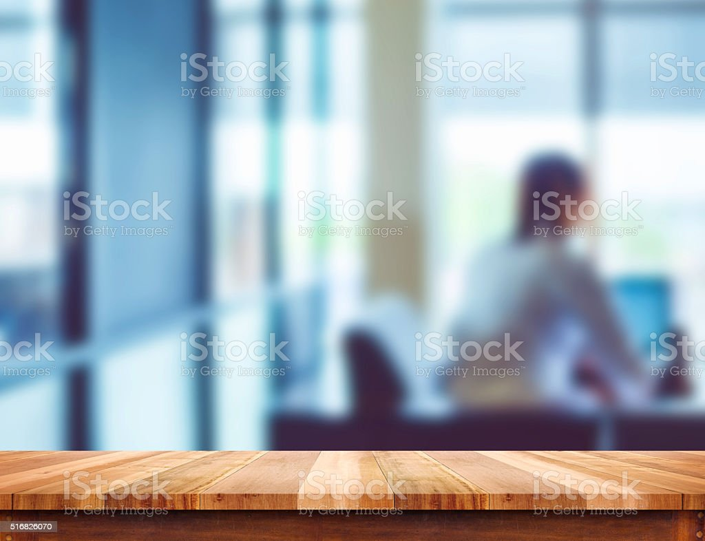 Empty light wood table top with blur office background stock photo