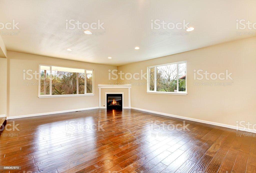 Empty living room with polished hardwood floor and corner fireplace. stock photo