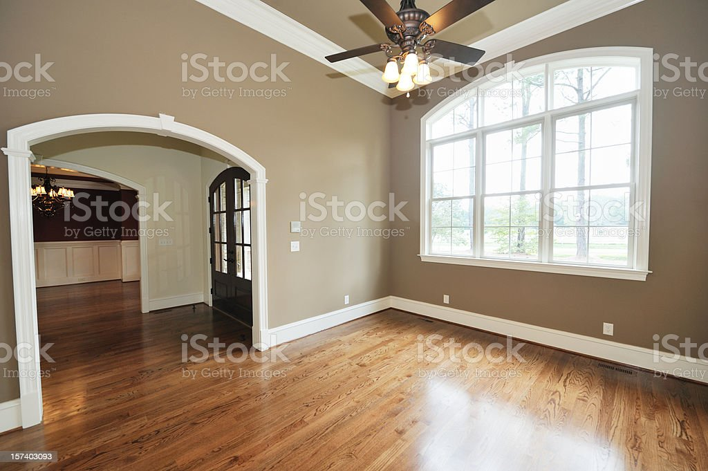 Empty living room with taupe walls and shiny hardwood floors royalty-free stock photo