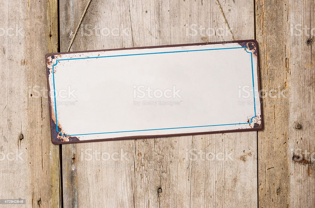 Empty metal sign in front of a rustic wooden wall stock photo