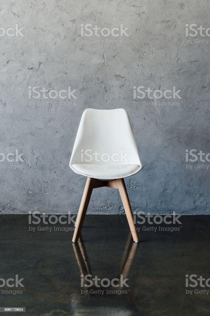 Empty modern white chair near grey wall in minimalistic style stock photo