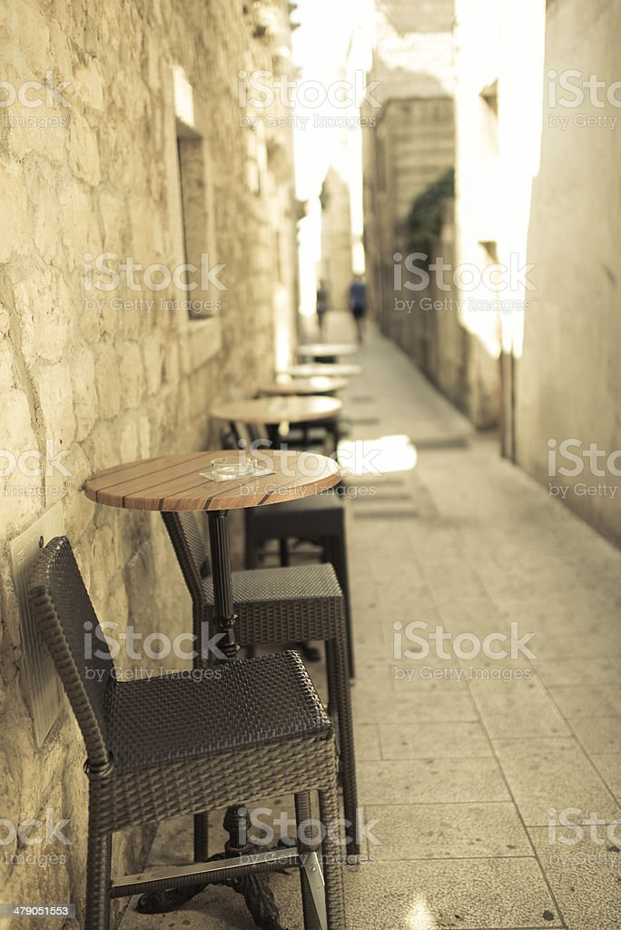 Empty narrow street of old town with caffee tables outdoors. stock photo