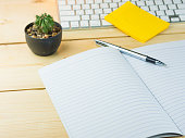 Empty notebook on work table with cactus, sticky note,