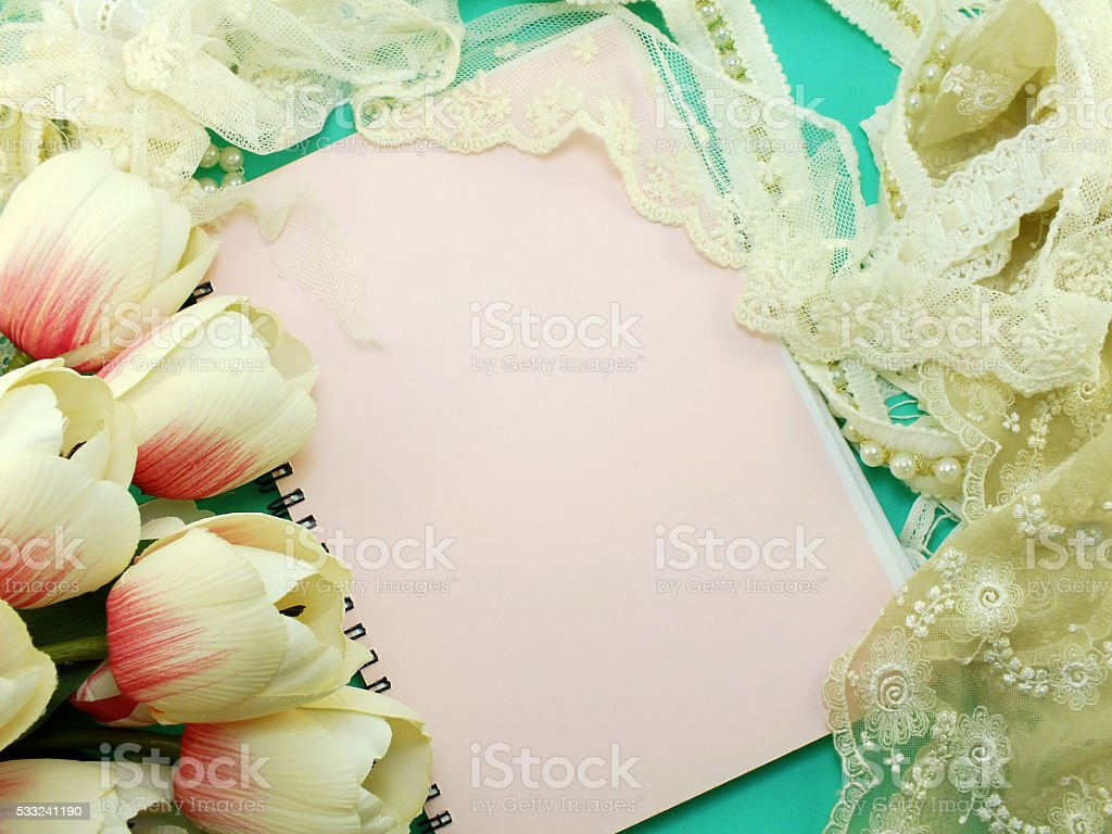 empty notebook with lace decor and artificial tulip flower background stock photo