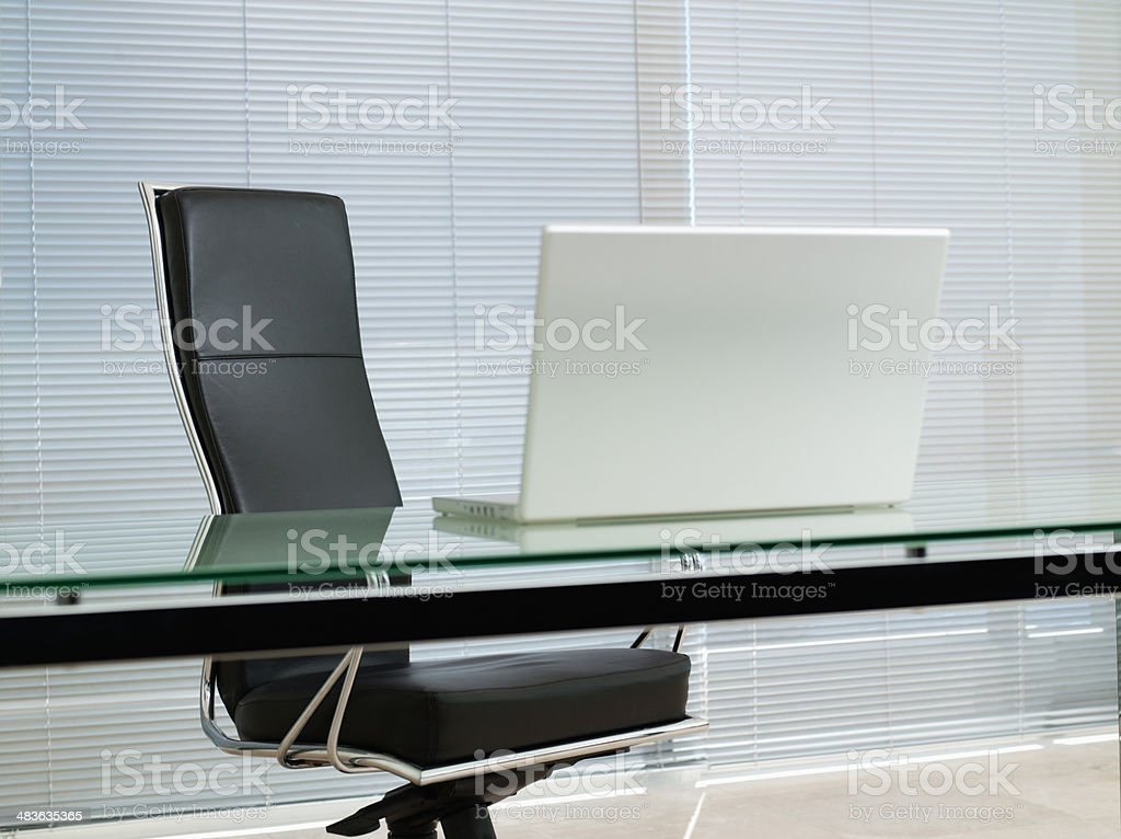 Empty office chair with laptop on desk stock photo