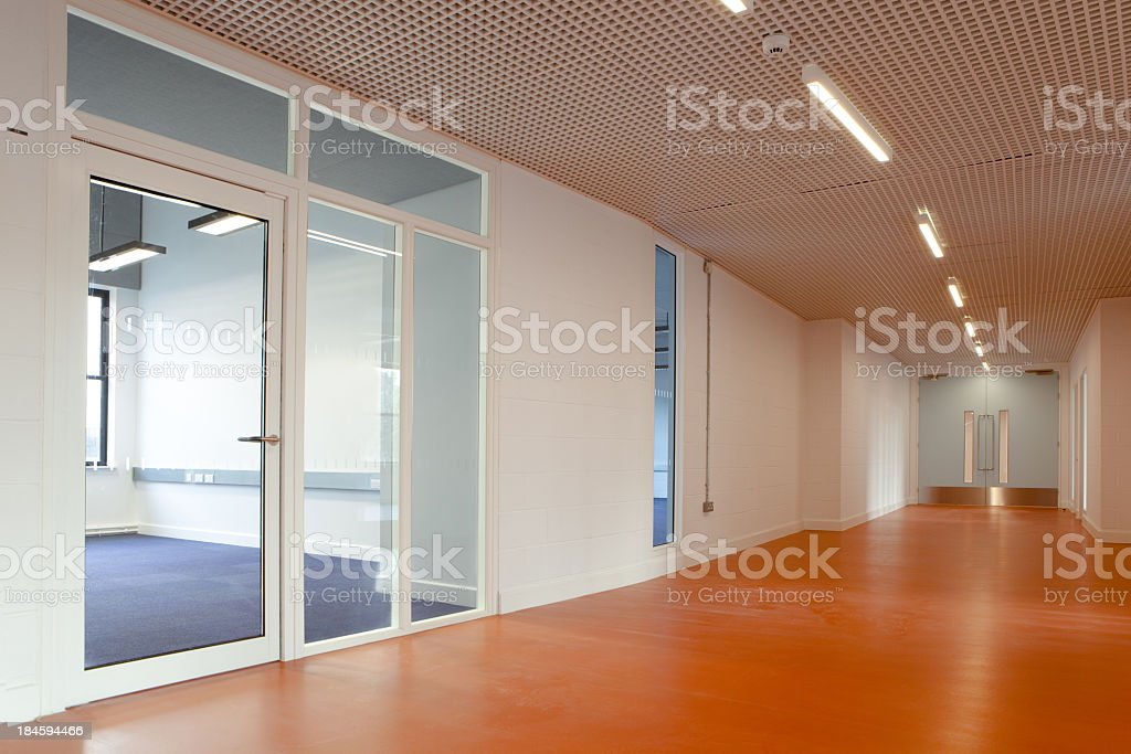 Empty office space featuring a laminate wood floor corridor stock photo