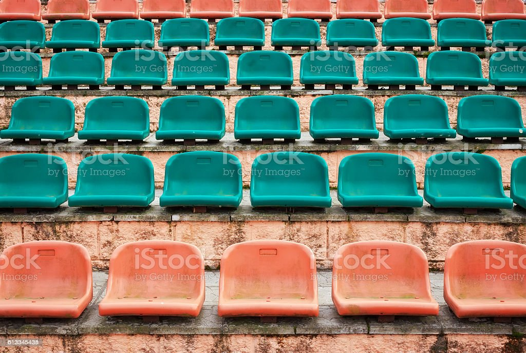 Empty old plastic seats at stadium, open door sports arena. stock photo