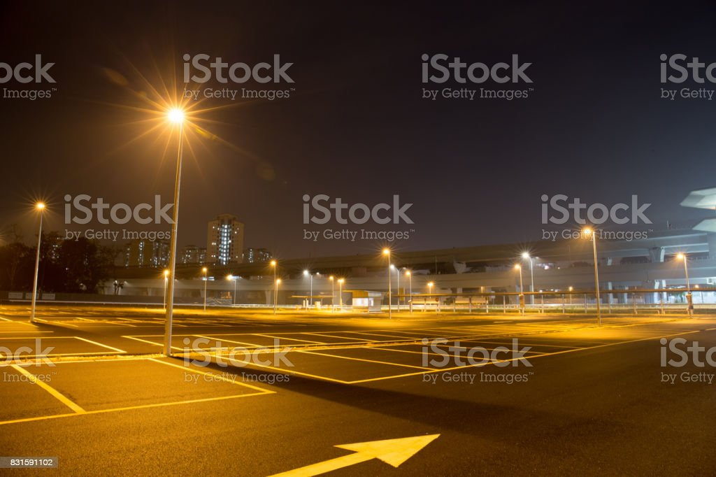 Empty outdoor car park at night shined with street lamps.