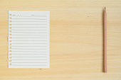 Empty paper note with pencil on wood background