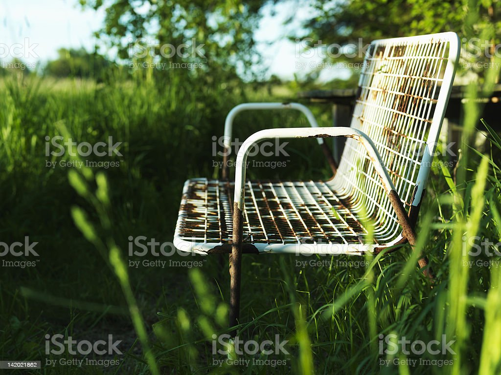 Empty park bench in grass stock photo