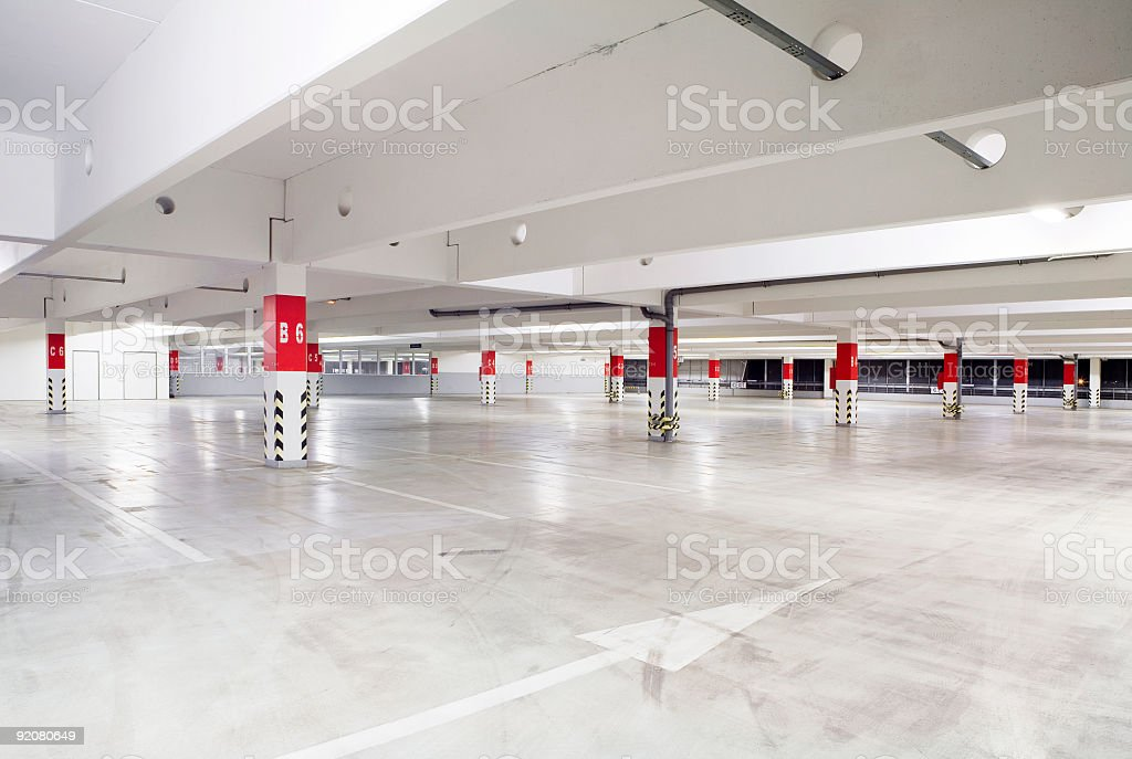 Empty parking garage with red and white pillars royalty-free stock photo