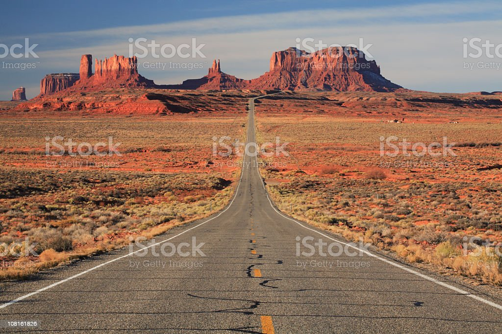 Empty paved road leading to Monument Valley stock photo