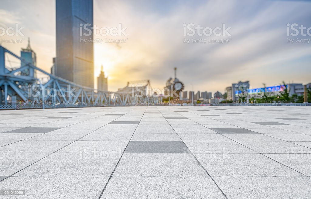 empty pavement and city skyline during sunset stock photo
