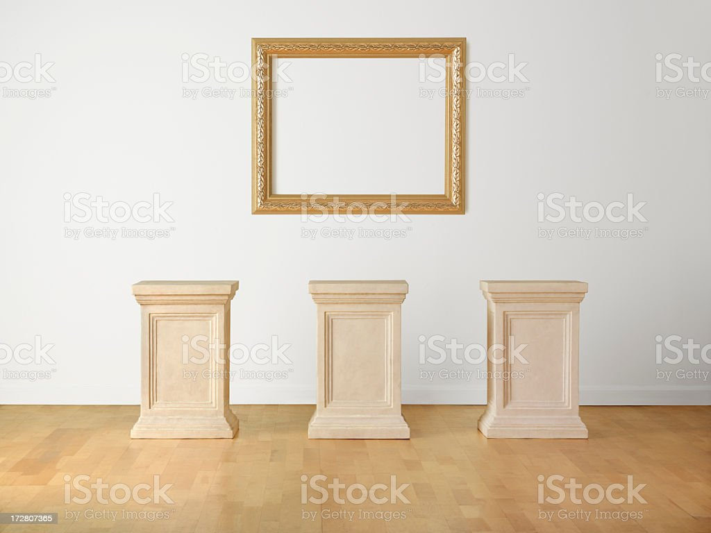 Empty picture frame and three empty pedestals in museum royalty-free stock photo
