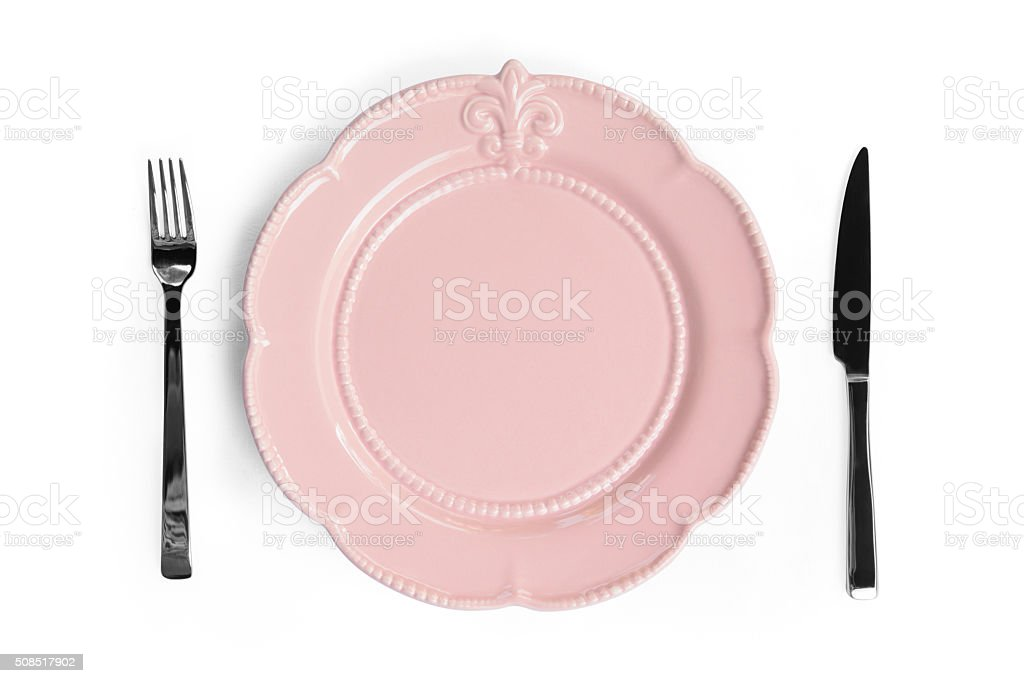Empty pink plate with a knife and fork stock photo
