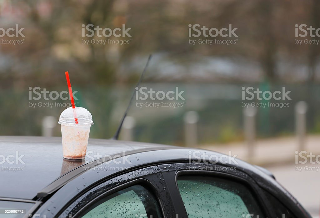 Empty plastic cup on the car's roof stock photo